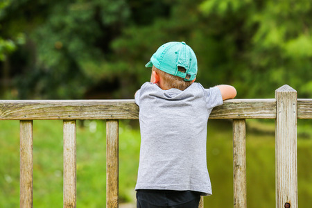A little boy leaning over a wooden fence in the park photo