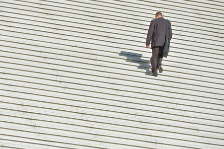 A man in business clothing climbing up along large endless stair photo