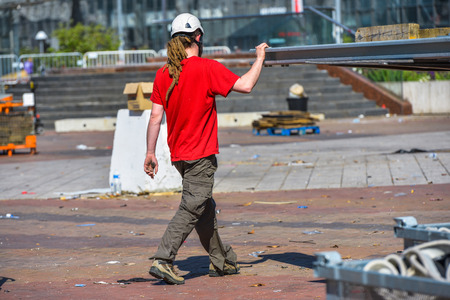 A construction worker with long dreadlocks holding a big metal platform in the air photo
