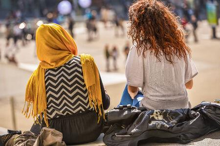 dat: Due ragazze che si siedono e che chiacchierano all'aperto su un autunno dat brillante