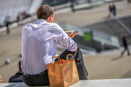 A young man in office outfit sittingn outdoors and having lunch while admiring city view photo