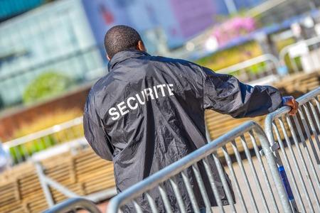 セキュリティ ワーカー金属フェンスの上に傾き、建築面積を見守る