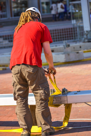 red tshirt: A construction worker with long dreadlocks and bright red t-shirt fastening a yellow hose