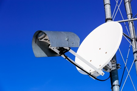 parabolic mirror: parabolic antenna off white against the blue sky