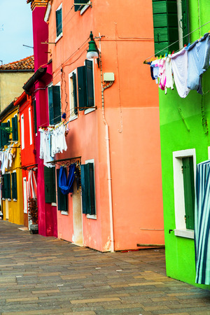 Colorful houses in Burano with the laundry drying on a wire photo