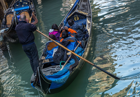 Venetian gondolier punting gondola while phoning through green canal waters of Venice Italy