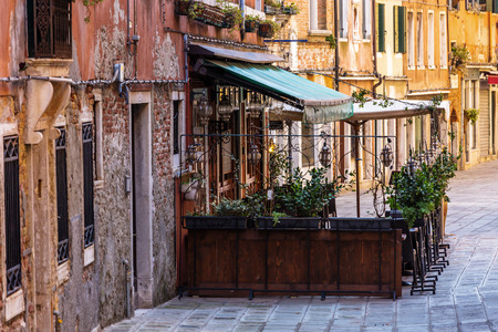 dinner cruise: Small restaurant among old houses in Venice, Italy. Stock Photo