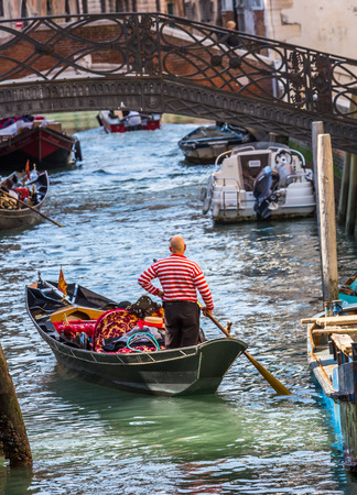 gondolier: Venetian gondolier punting gondola through green canal waters of Venice Italy Editorial