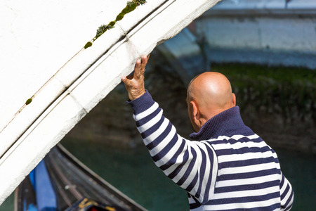 punting: Closeup on Venetian gondolier punting his hand on a bridge of Venice Italy Stock Photo
