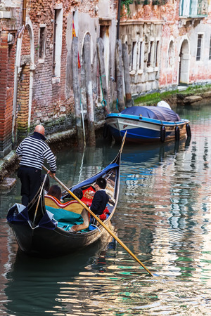 punting: Venetian gondolier punting gondola through green canal waters of Venice Italy Editorial