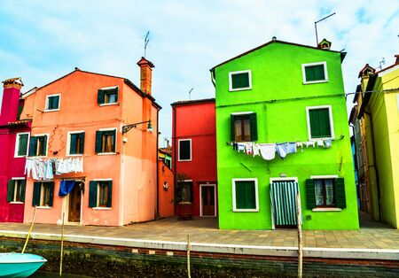 BURANO, ITALY - MAR 20 - Colorful houses in Burano with the laundry drying on a wirenear Venice on Mars 20, 2015, Italy.