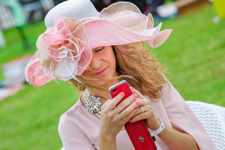boater: CHANTILLY - JUNE 15: Lovely woman with a pretty hat phoning - The Diana Award is a French horse race qui runs Every year in June. In an atmosphere of sporting fervor and chic picnic Chantilly. Considered the price of elegance and distinction, thanks to ic Editorial