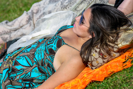 qui: CHANTILLY - JUNE 15: Stylish woman lying on the grass at the Prix de Diane - The Prix de Diane horse race is a French qui runs Every year in June. In an atmosphere of sporting fervor and chic picnic Chantilly. Considered the price of elegance and distinct Editorial