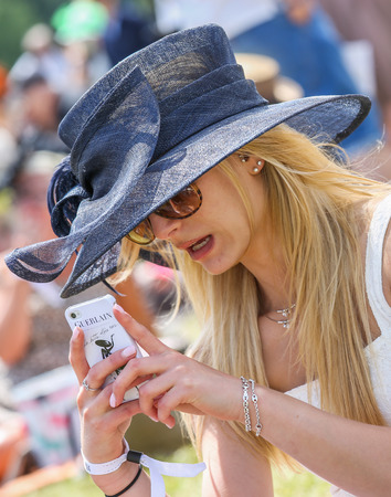 chantilly: CHANTILLY - JUNE 15: Lovely woman with a pretty hat phoning - The Diana Award is a French horse race qui runs Every year in June. In an atmosphere of sporting fervor and chic picnic Chantilly. Considered the price of elegance and distinction, thanks to ic Editorial