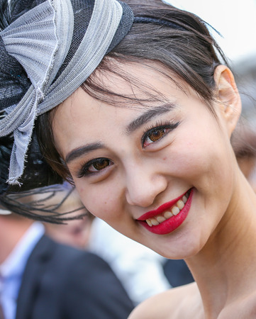 bourgeoisie: CHANTILLY - JUNE 15: Lovely asian woman with a pretty hat at the Prix de Diane - The Diana Award is a French horse race qui runs Every year in June. In an atmosphere of sporting fervor and chic picnic Chantilly. Considered the price of elegance and distin