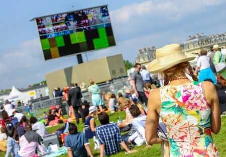 bourgeoisie: CHANTILLY - JUNE 15: Back of lovely woman with a pretty hat at the Prix de Diane - The Prix de Diane horse race is a French who runs Every year in June. In an atmosphere of sporting fervor and chic picnic Chantilly. Considered the price of elegance and di