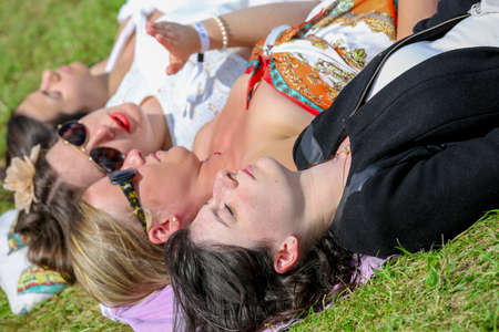 bourgeoisie: CHANTILLY - JUNE 15: Pretty girls group lying on the grass at the Prix de Diane - The Prix de Diane horse race is a French who runs Every year in June. In an atmosphere of sporting fervor and chic picnic Chantilly. Considered the price of elegance and dis