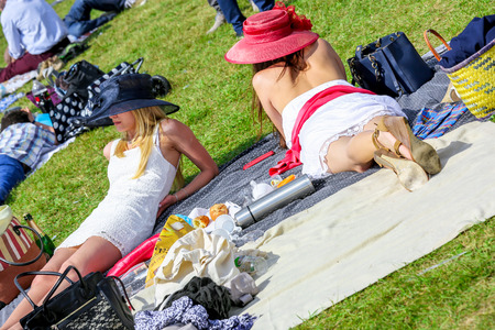 chantilly: CHANTILLY - JUNE 15: Pretty girls lying on the grass at the Prix de Diane - The Prix de Diane horse race is a French who runs Every year in June. In an atmosphere of sporting fervor and chic picnic Chantilly. Considered the price of elegance and distincti