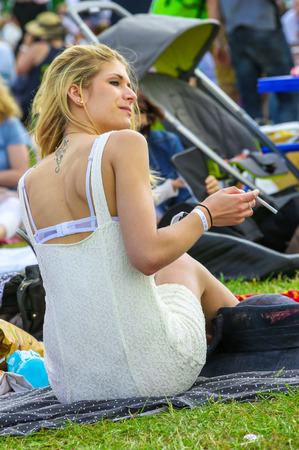 bourgeoisie: CHANTILLY - JUNE 15: Pretty girl lying on the grass at the Prix de Diane - The Prix de Diane horse race is a French who runs Every year in June. In an atmosphere of sporting fervor and chic picnic Chantilly. Considered the price of elegance and distinctio