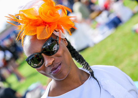 chantilly: CHANTILLY - JUNE 15: Lovely black woman with a pretty hat at the Prix de Diane - The Diana Award is a French horse race qui runs Every year in June. In an atmosphere of sporting fervor and chic picnic Chantilly. Considered the price of elegance and distin Editorial