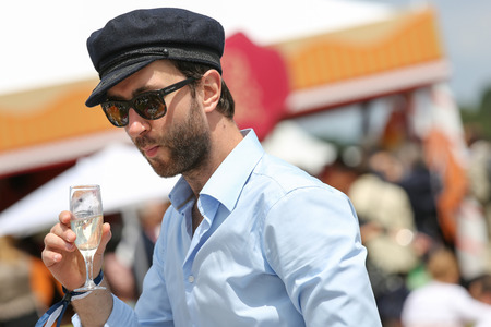 chantilly: CHANTILLY - JUNE 15: Cute boy with a glass of champagne in hand at the Prix de Diane - The Prix de Diane horse race is a French qui runs Every year in June. In an atmosphere of sporting fervor and chic picnic Chantilly. Considered the price of elegance an Editorial