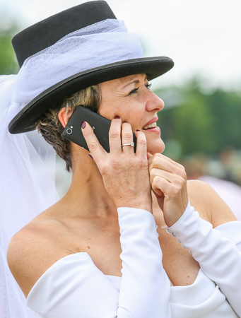 bourgeoisie: CHANTILLY - JUNE 15: Lovely woman with a pretty hat phoning at the Prix de Diane - The Prix de Diane horse race is a French Who runs Every year in June. In an atmosphere of sporting fervor and chic picnic Chantilly. Considered the price of elegance and di