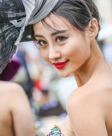 qui: CHANTILLY - JUNE 15: Lovely asian woman with a pretty hat at the Prix de Diane - The Diana Award is a French horse race qui runs Every year in June. In an atmosphere of sporting fervor and chic picnic Chantilly. Considered the price of elegance and distin