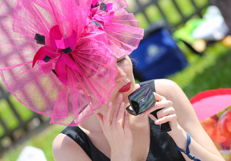 chantilly: CHANTILLY - JUNE 15: Beautiful and elegant woman powdering her face at the Prix de Diane - The Diana Award is a French horse race qui runs Every year in June. In an atmosphere of sporting fervor and chic picnic Chantilly. Considered the price of elegance  Editorial