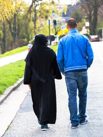 Jong moslimpaar dat in de straat loopt