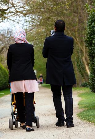 Moslim paar lopen met hun kinderen in een wandelwagen