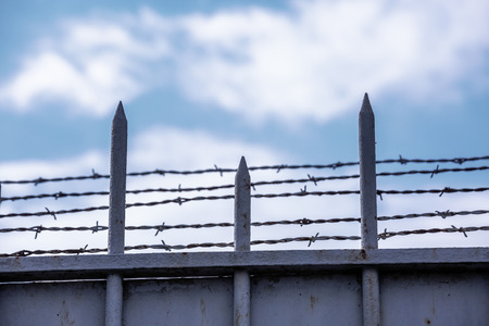 totalitarianism: gate with barbed wire on blue sky background