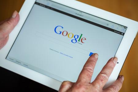 Paris, França - 27 de abril de 2015: Mulher sênior que usa o tablet com o Google busca home page em uma tela ipad