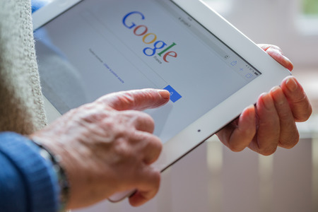 google chrome: Paris, France - April 27, 2015: Senior woman using tablet with Google search home page on a ipad screen
