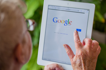 google: Paris, France - April 27, 2015: Senior woman using tablet with Google search home page on a ipad screen