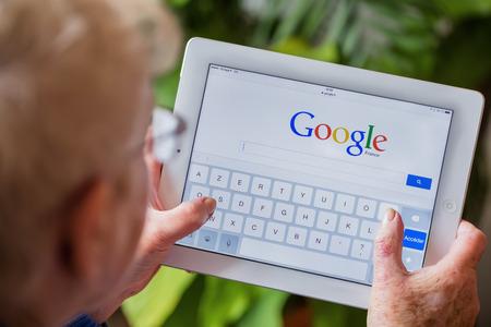 tercera edad: París, Francia - 27 abril 2015: Mujer mayor que usa la tableta con la página de búsqueda principal de Google en una pantalla del ipad Editorial
