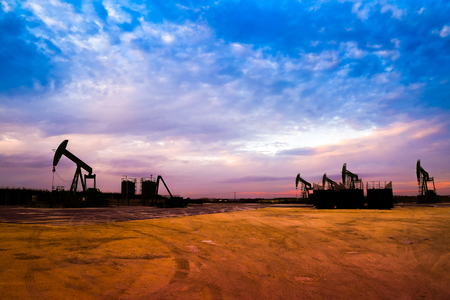 Silhouette of Oil pumps at oil field with nice sunset sky background Stock Photo