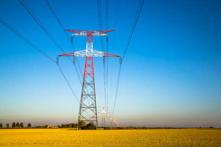 Electricity transmission pylon silhouetted against blue