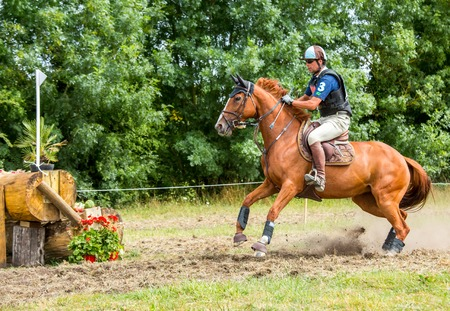 horseman: Saint Cyr du Doret, France - July 29, 2016: Horseman riding horse over an obstacle on cross country event Editorial