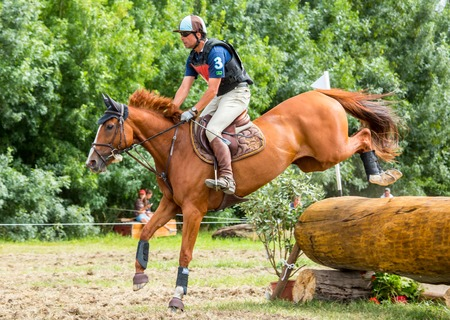 eventing: Saint Cyr du Doret, France - July 29, 2016: Horseman riding horse over an obstacle on cross country event Editorial