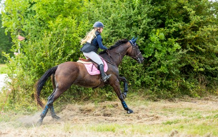 eventing: Saint Cyr du Doret, France - July 29, 2016: Rider on her galloping horse during a cross country manisfestation