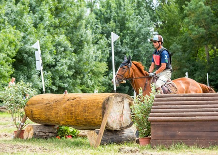 uomo a cavallo: Saint Cyr du Doret, France - July 29, 2016: Horseman riding horse over an obstacle on cross country event Editoriali