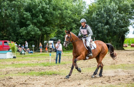 eventing: Saint Cyr du Doret, France - July 29, 2016: Rider on his galloping horse during a cross country manisfestation