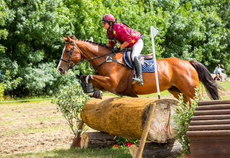 eventing: Saint Cyr du Doret, France - July 29, 2016: Woman riding horse over obstacle on cross country event