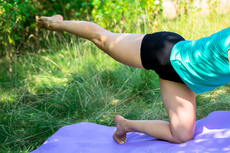 exercice: A individual performing the side knee posture on her yoga mat outside Stock Photo