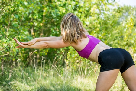 A blonde haired woman outside performing a side hand  yoga position while standing