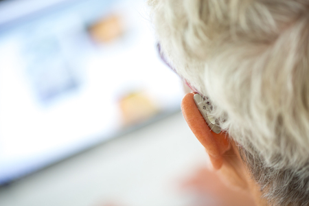 closeup senior woman wearing hearing aid in her ears in front a laptop Stock Photo