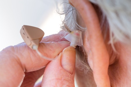 hearing aid: closeup senior woman inserting hearing aid in her ears