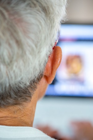 infotech: An old person with a pair of glasses in front of a laptop screen