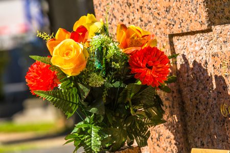 Des fleurs sur une des pierres tombales dans un cimetière avec des centaines de pierres tombales en arrière-plan
