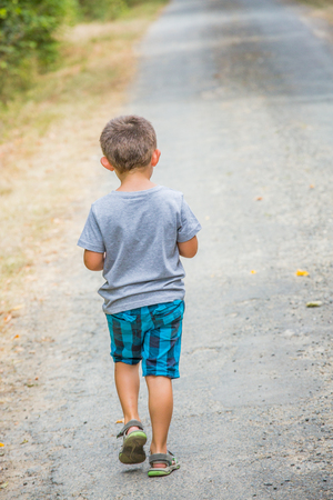 vexation: Young child walking back alone on a country road